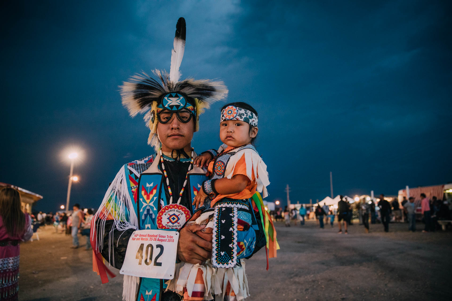 american-indian-fancy-dancer-with-feather-holding-child.JPG