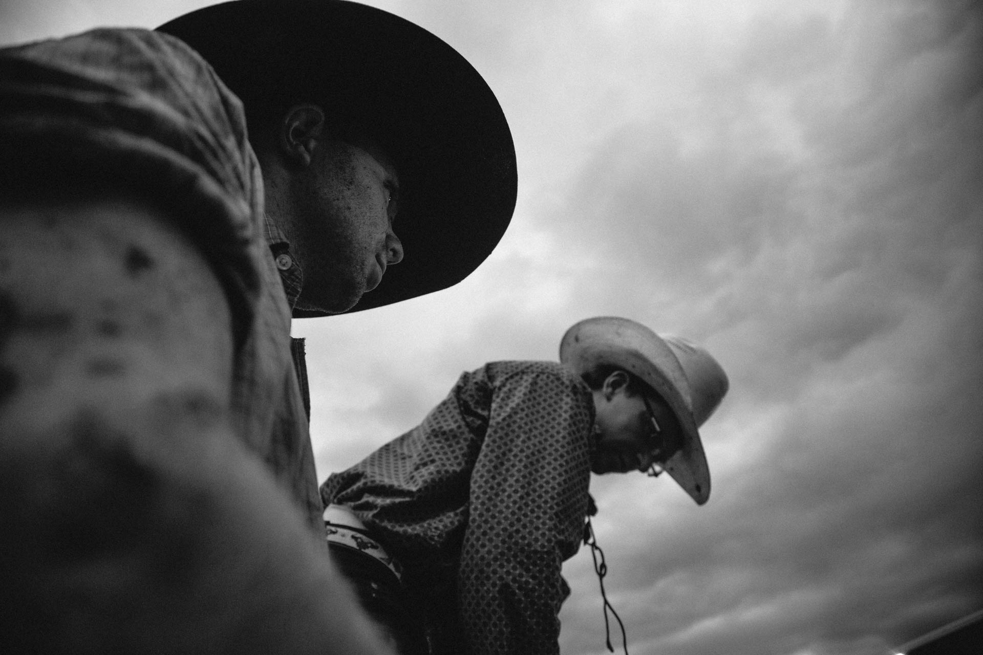cowboys-covered-in-mud-prepare-for-thebull-dramatic-skies-a5059