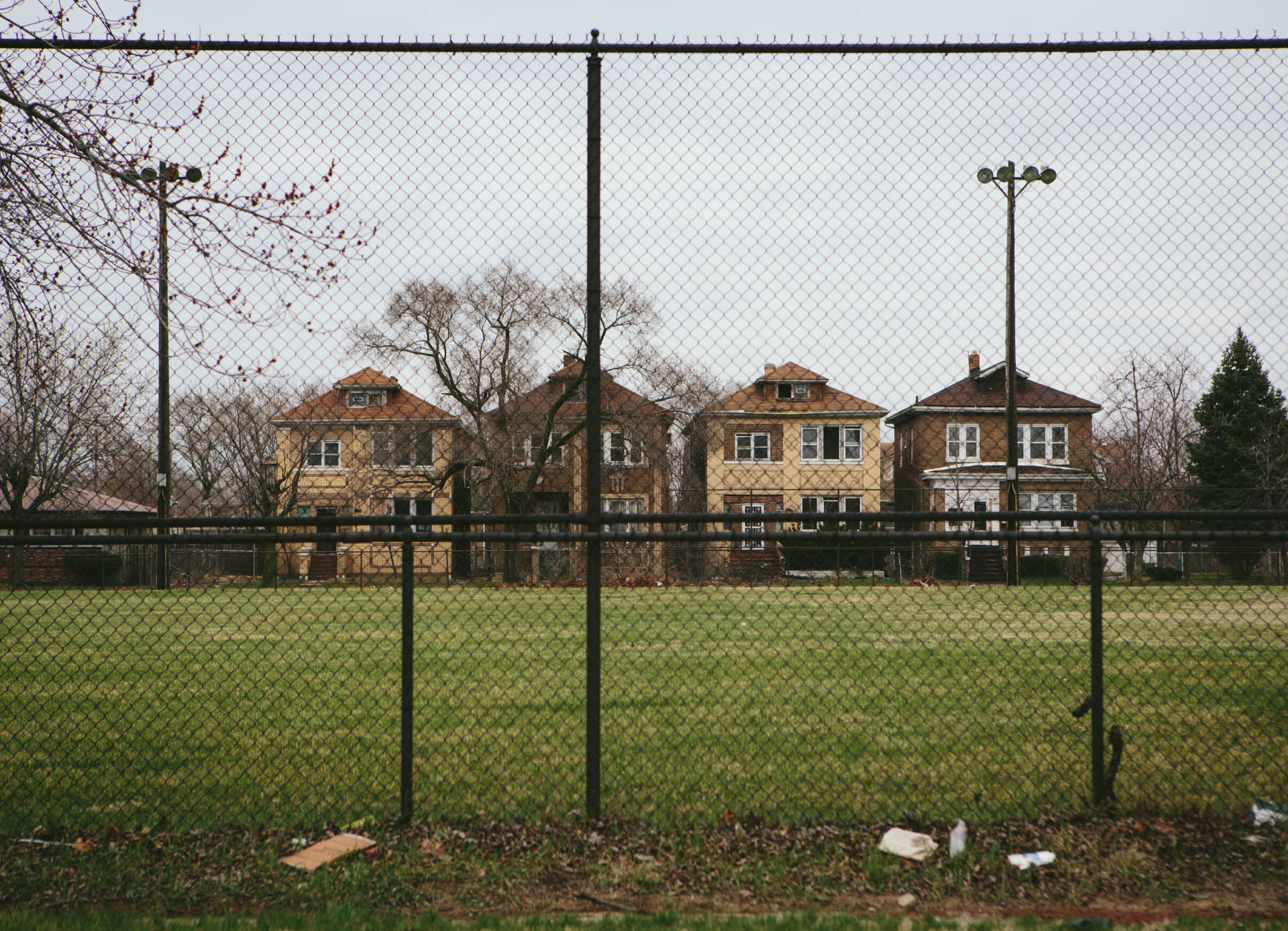 row-of-square-brick-homes-behind-chainlink-fence-gary-in-6058