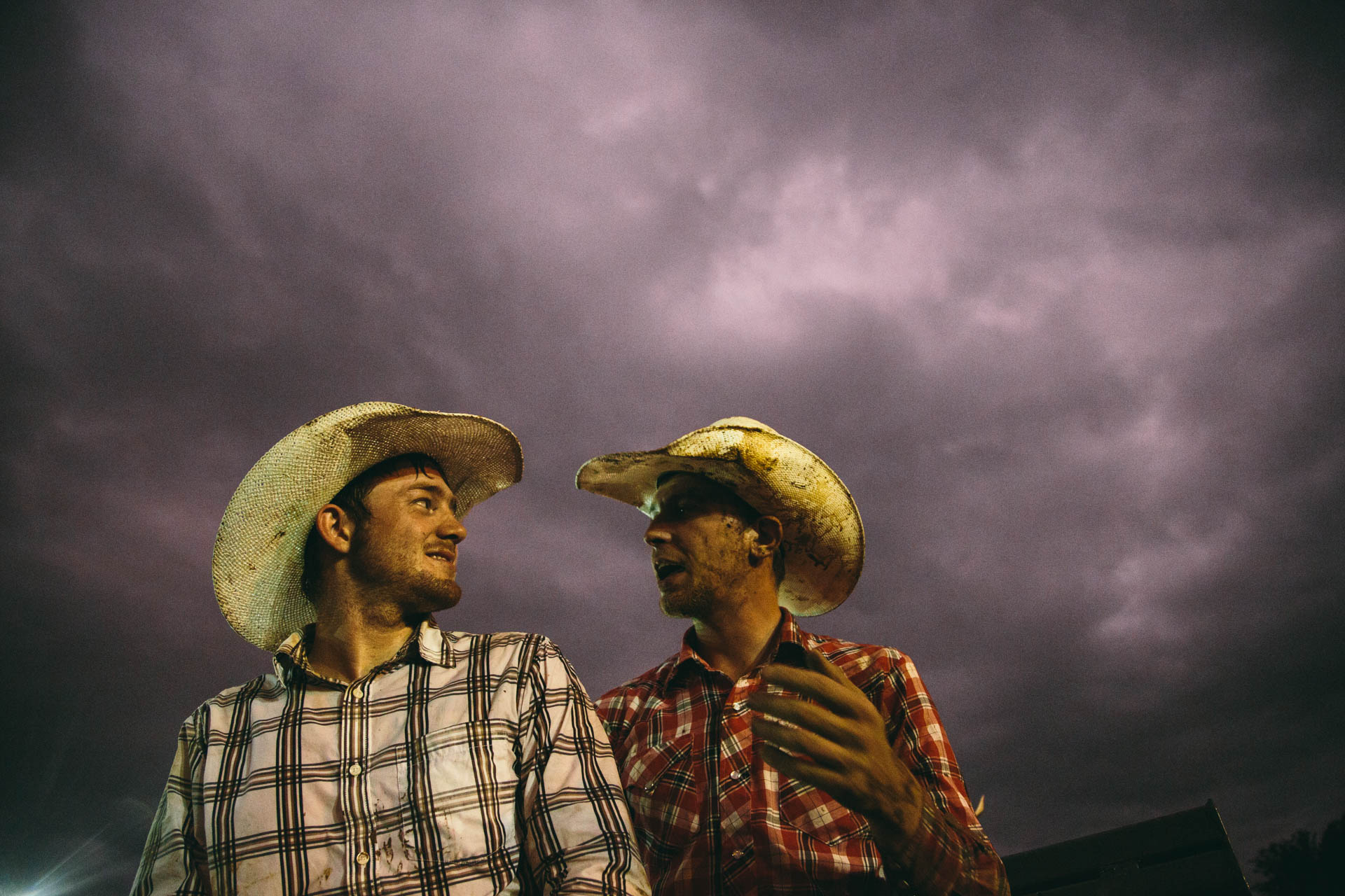 two-cowboys-talk-rodeo-stormy-skies-western-shirts-covered-in-mud-night-a5179