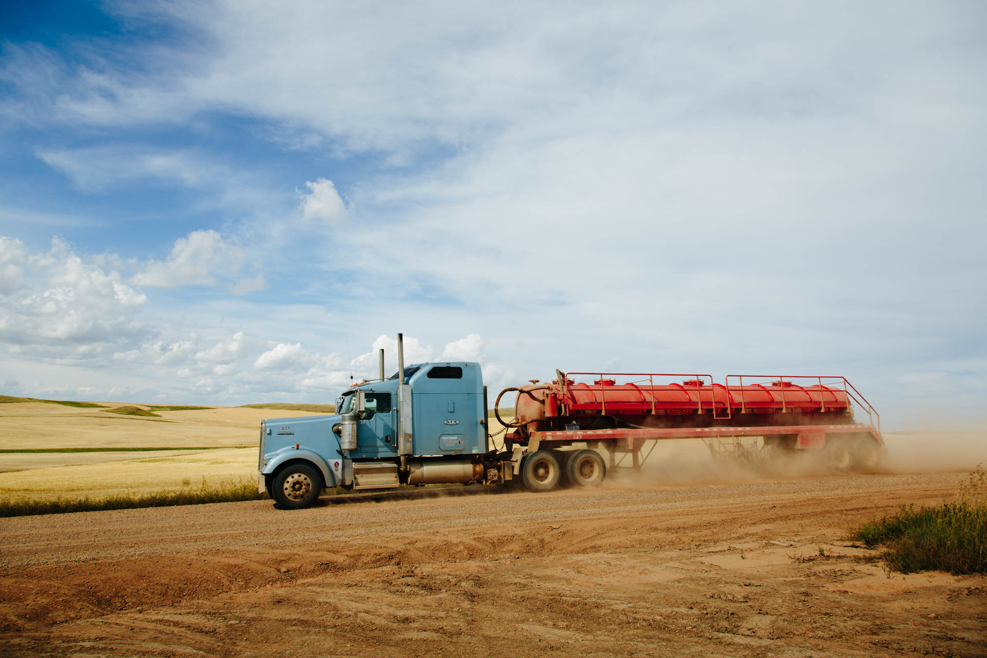 water-semi-kicks-up-dust-dirt-road-red-tank